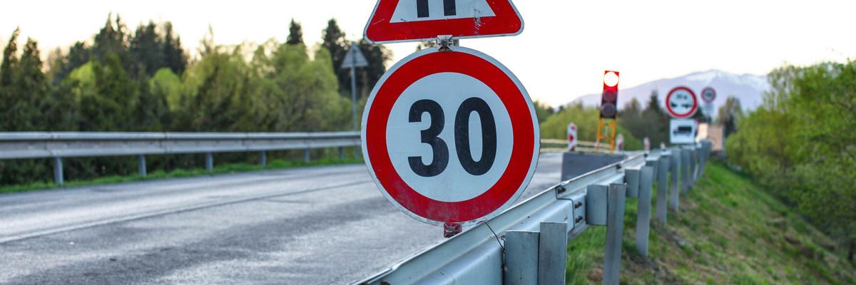Запрещающий дорожный знак возле дороги